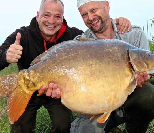 Einer der größten Kanal-Karpfen, die je in Ostfriesland gefangen wurden: Zusammen mit Matze freut sich Markus Lotz (li.) über den 20,3 Kilo schweren Brocken.