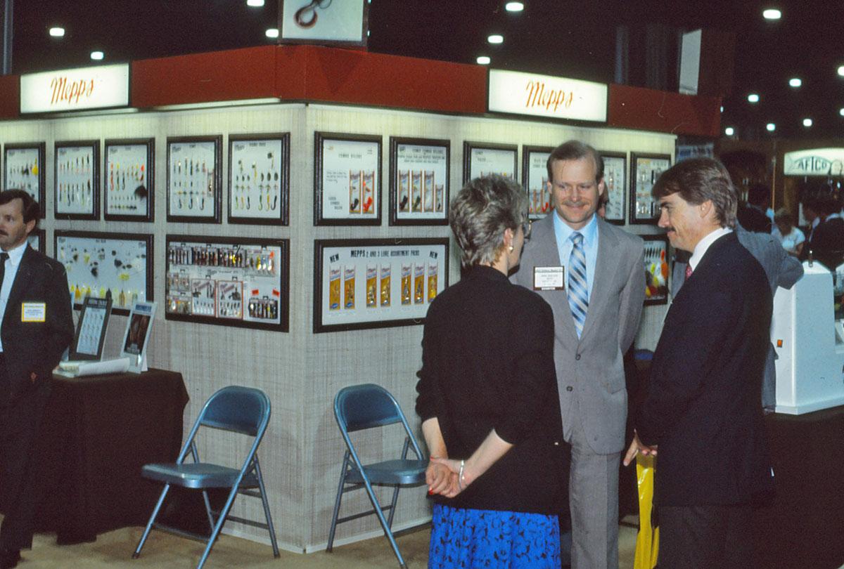 Mike Sheldon (grauer Anzug) im Gespräch mit Fachhändlern auf einer AFTMA-Messe.
