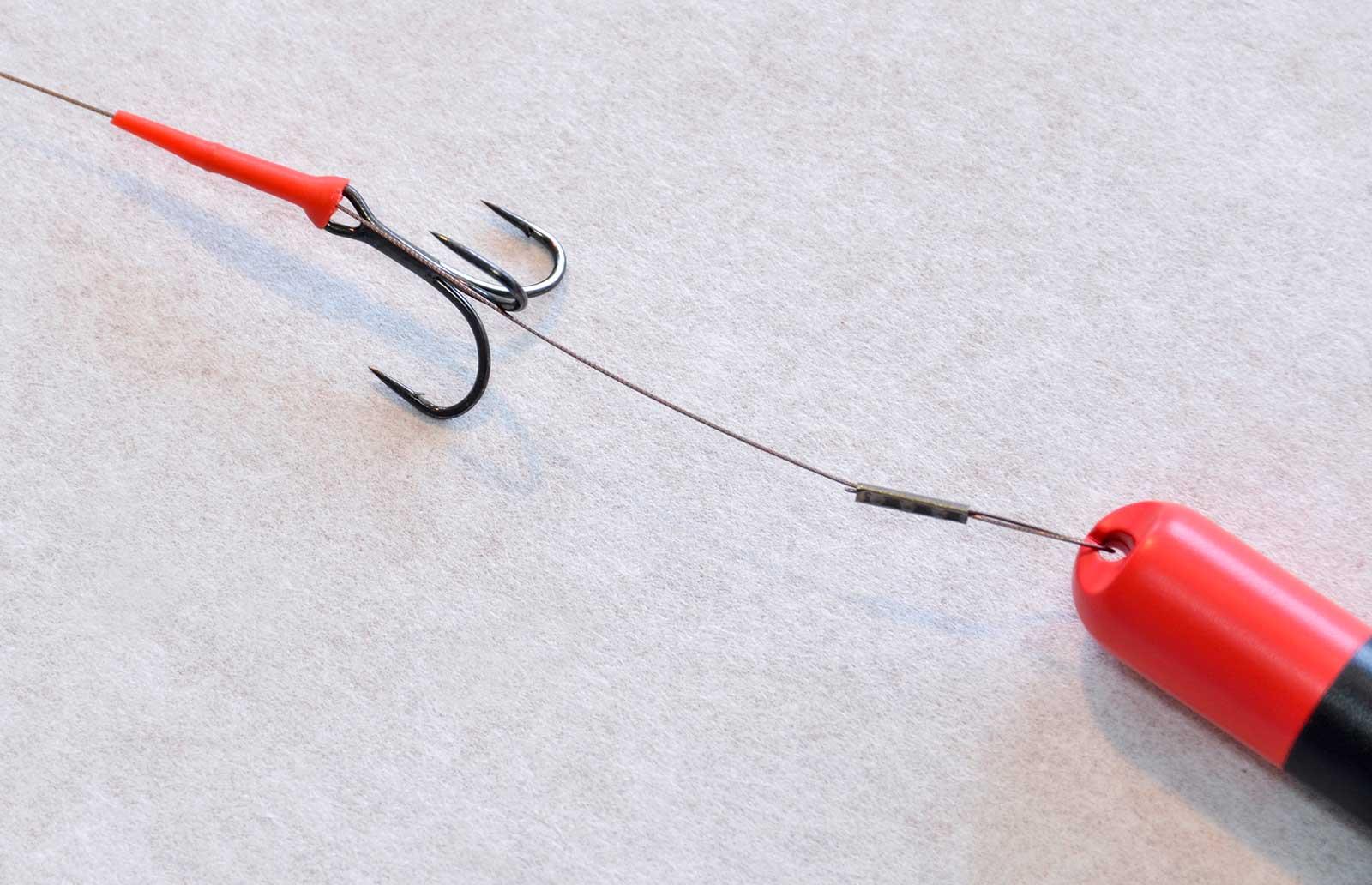 Wichtig: Den Gummischlauch muss man mit dosierter Gewalt über Hülse und Drilling schieben. Aber Vorsicht - schnell kann man sich dabei einen Haken in den Finger jagen!