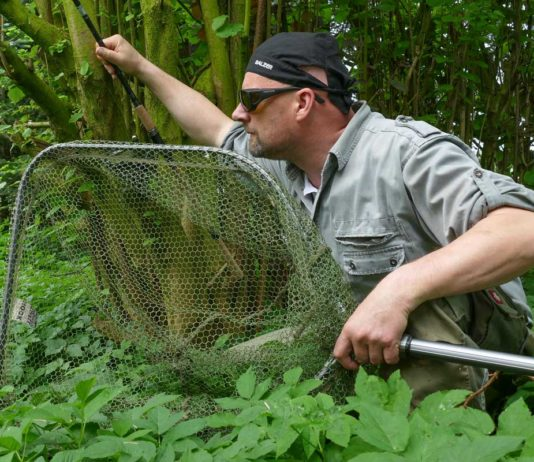 Matze hat einen Karpfen an der Oberfläche entdeckt. Mit montierter Rute und handlichem Raubfischkescher pirscht er sich ran.