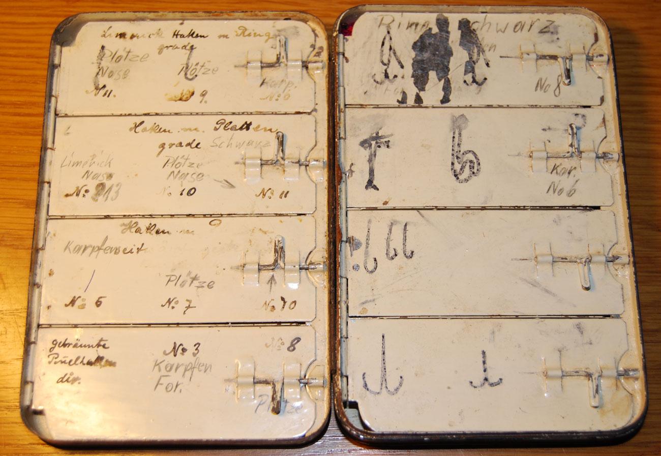 Die blecherne Fliegenbox aus der Vorkriegszeit ist auf und in den Fächern beschriftet, mit einer alten Schreibschrift in Tusche und einer neueren Druckschrift in Bleistift.