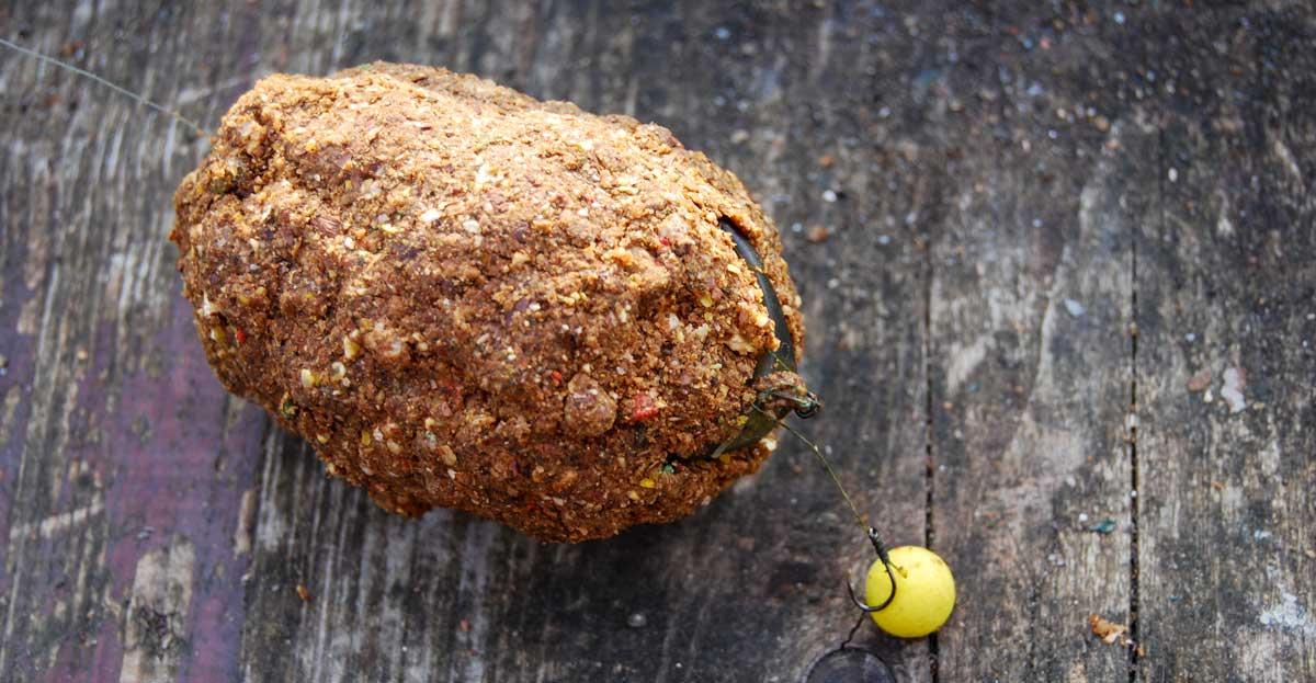 Das Vorfach knetet man in den Futter- ballen am Method Feeder ein. Gelbe Köder, hier ein kleiner Pop-up-Boilie, heben sich gut vom Futter ab.
