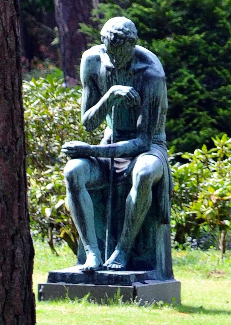"""Die lebensgroße Bronzeplastik """"Der müde Wanderer"""" von H. v. Ophemert steht in Holland auf einem Friedhof."""